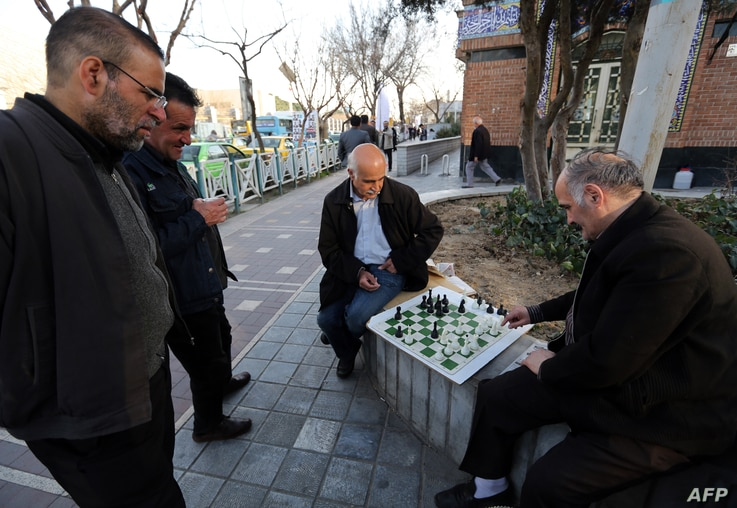 Iranian men play chess in a street in Tehran on February 23, 2016. (Photo by ATTA KENARE / AFP)