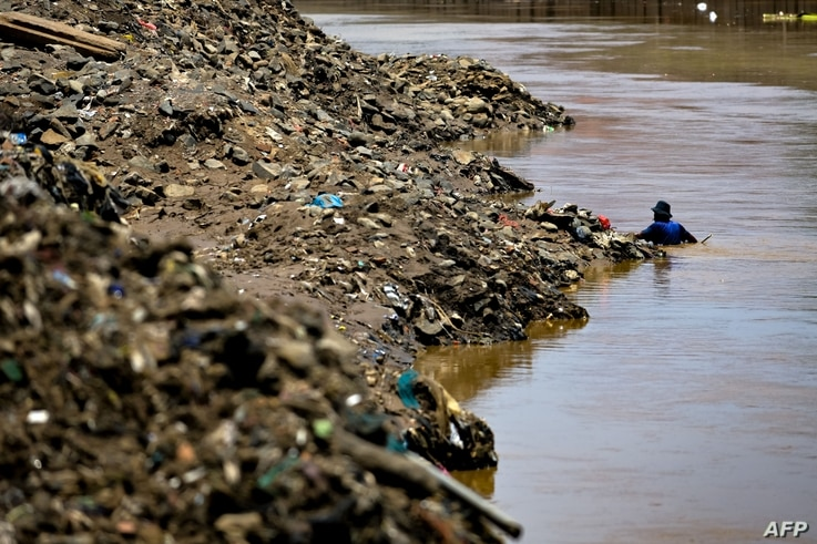 A man scavenges along a river for household plastic waste to be sold for recycling in Jakarta on September 23, 2020. (Photo by…