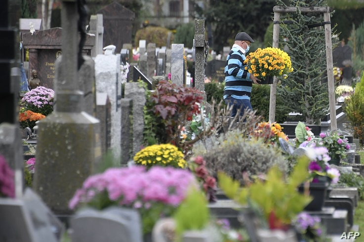 A man carries flowers in a cemetery in Strasbourg, eastern France on November 1, 2020, during All Saint's day festivities as…