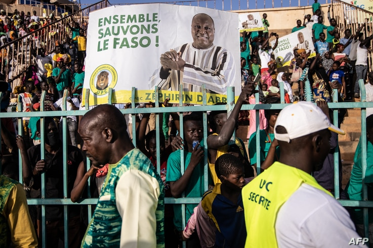 Supporters hold placards and cheer Burkina Faso's presidential candidate Zephirin Diabre during a rally in Ouagadougou on…
