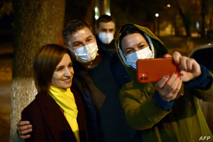 Moldova's presidential candidate Maia Sandu poses for a selfie photo with her supporters as she leaves the Action and…