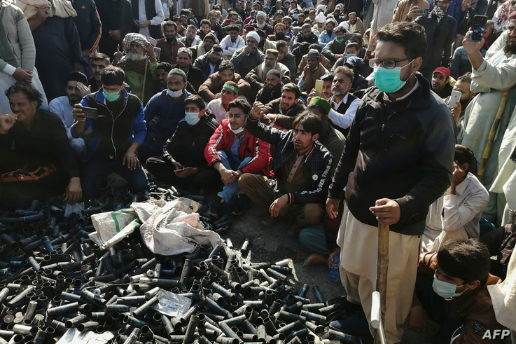 Activists and supporters of Tehreek-e-Labbaik Pakistan (TLP), a religious party, gather beside empty tear gas shells fired by…