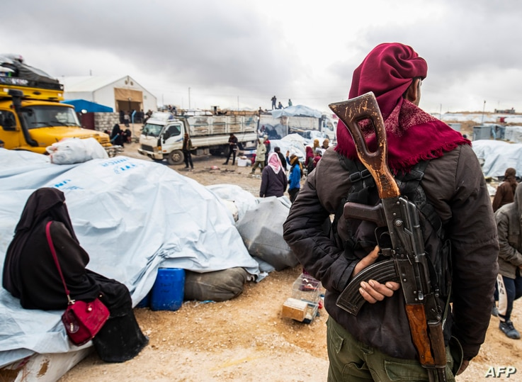 A member of Kurdish security forces watches as families load their belongings onto trucks before leaving the Kurdish-run al-Hol…