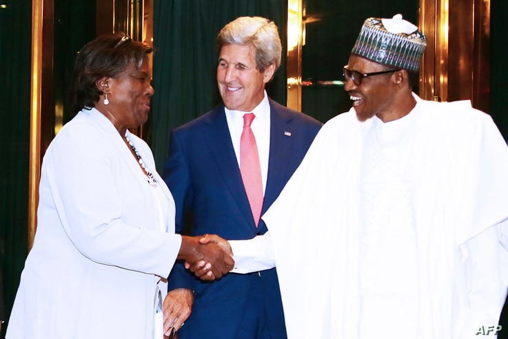 United States Secretary of State John Kerry (C) reacts as Nigerian President Muhammadu Buhari (R) shakes hands with Assistant…