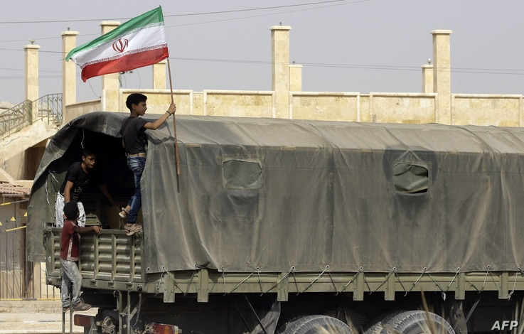 A Syrian boy holds the Iranian flag as a truck carrying aid provided by Iran arrives in the eastern city of Deir Ezzor on…