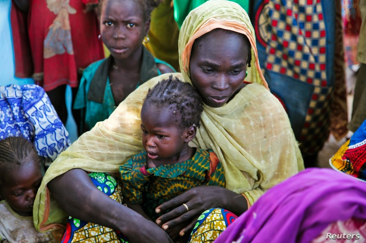 A mother and her child sit with other families at a camp for internally displaced people after a dam broke near their village…