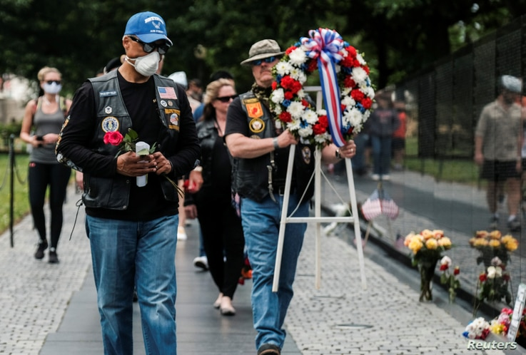 U.S. veterans, some wearing protective face masks in the midst of the coronavirus disease (COVID-19) pandemic, carry a wreath.