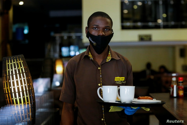 John Brian, an employee at Cafe Deli Restaurant delivers an order during the reopening after weeks of lockdown restrictions…