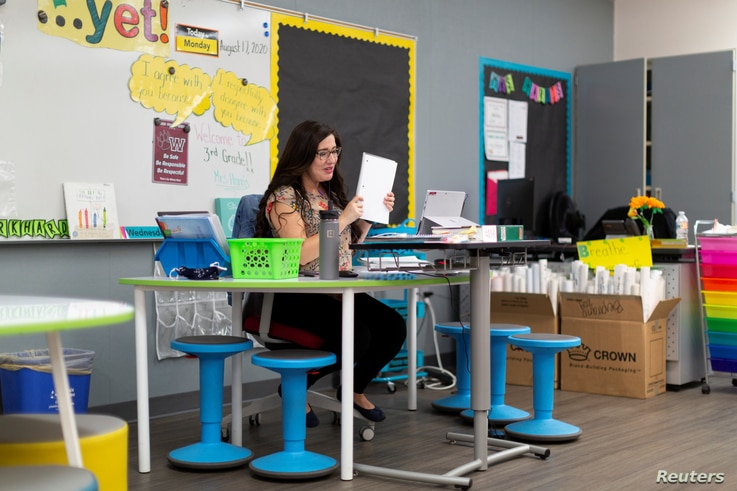 Ruth Harris virtually teaches a third grade class for students who are either at home or in a separate classroom as in-person…