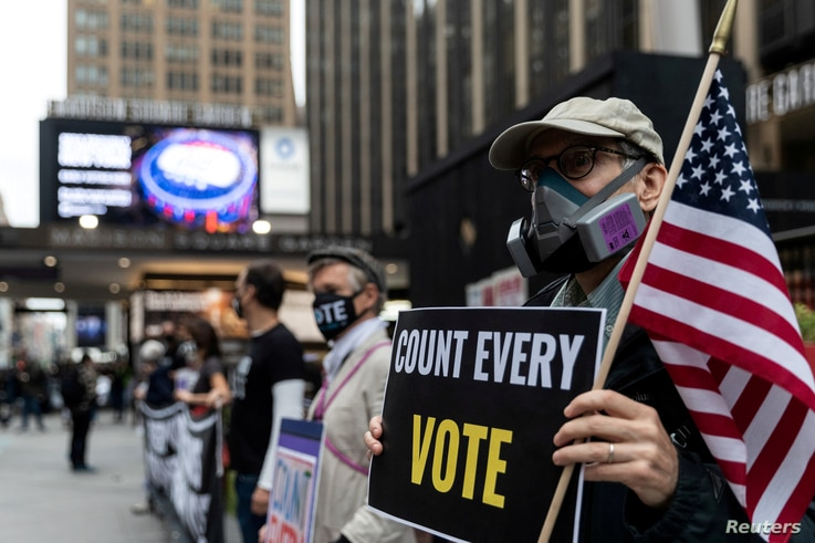 FILE PHOTO: A man wearing a protective mask due to COVID-19 pandemic holds a sign outside Madison Square Garden, which is used…