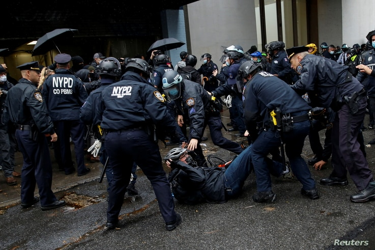 A man is detained while Black Lives Matter members and people confront NYPD during a march against far right movement and Trump…