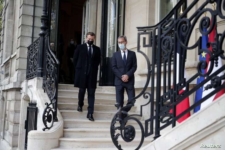 French President Emmanuel Macron speaks with Deputy Head of Mission at the Austrian Embassy Wolfgang Wagner after signing a…