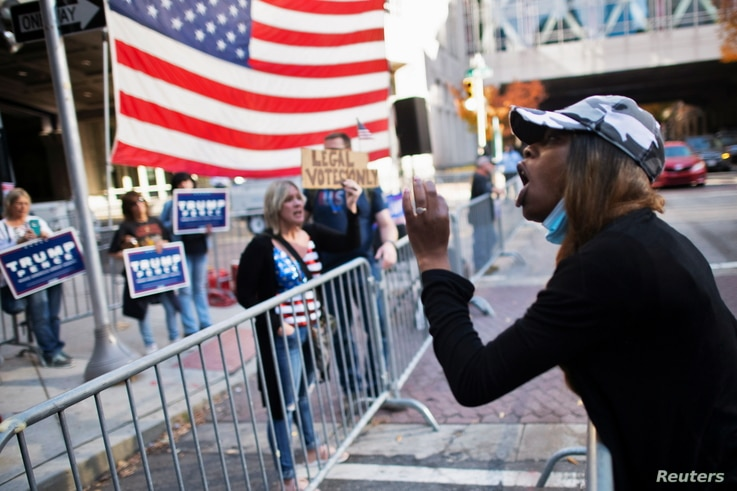 Jessica Ashley, 32, a supporter of President-elect Joe Biden, shouts towards supporters of U.S. President Donald Trump.