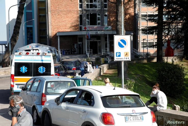 People wait next to their cars outside the Cotugno hospital as the battle with the coronavirus disease (COVID-19) intensifies,…
