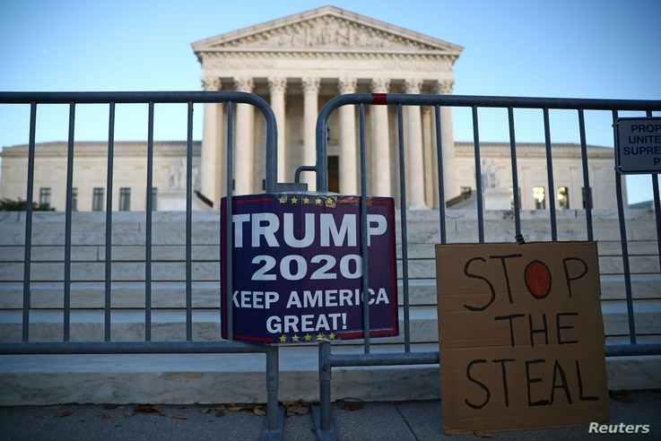 Signs by supporters of U.S. President Donald Trump hang outside the U.S. Supreme Court building in Washington, U.S. November 10…