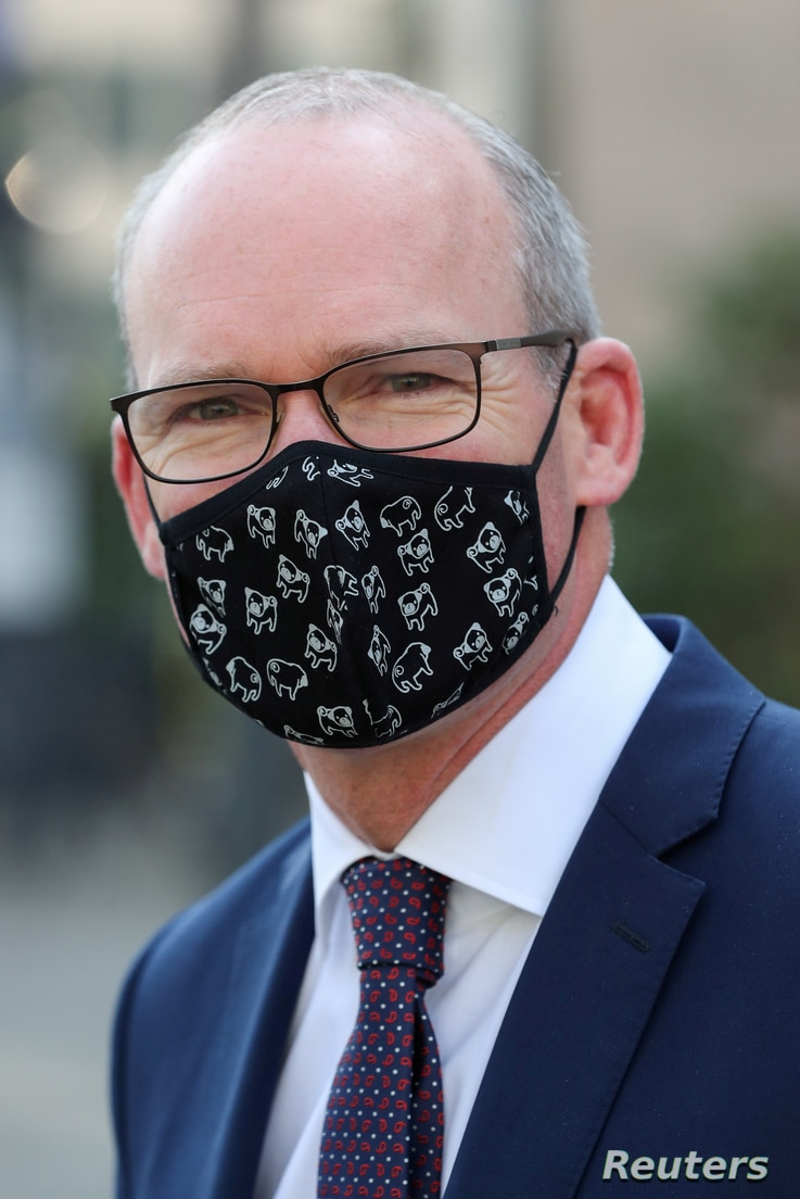 FILE PHOTO: Irish Foreign Minister Simon Coveney wearing a face mask, is seen after a European general affairs ministers…