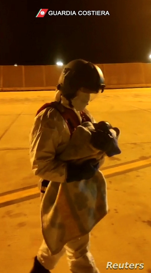 Italian coast guard member holds a child who was evacuated from the Spanish search and rescue ship Open Arms after being…