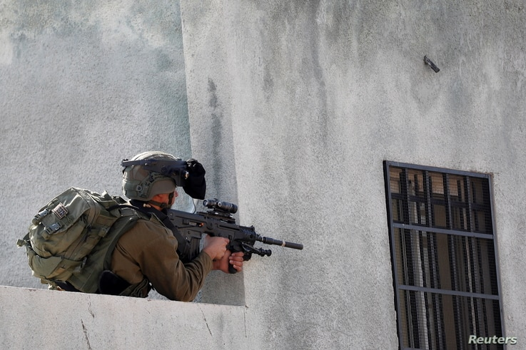 An Israeli soldier points his weapon during a Palestinian protest against Jewish settlements, in Kafr Qaddum in the Israeli-occupied West Bank, Nov. 13, 2020.