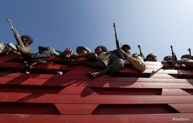 FILE PHOTO: Members of Amhara region militias ride on their truck as they head to the mission to face the Tigray People's…