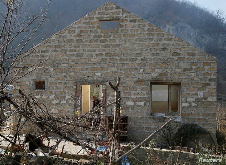 A man is seen inside a destroyed house in the village of Knaravan located in a territory which is soon to be turned over to…