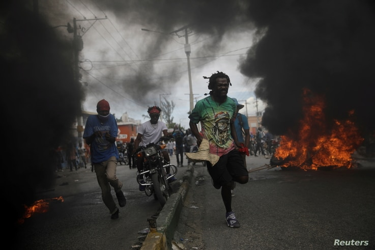 Protestors run past burning tires during a march demanding the resignation of Haiti's President Jovenel Moise.