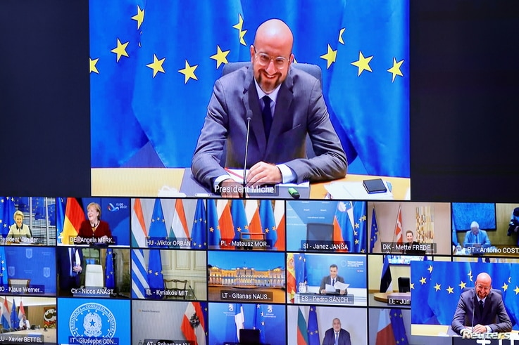 European Council President Charles Michel is seen on a screen as he speaks with EU leaders during an EU Summit video conference…