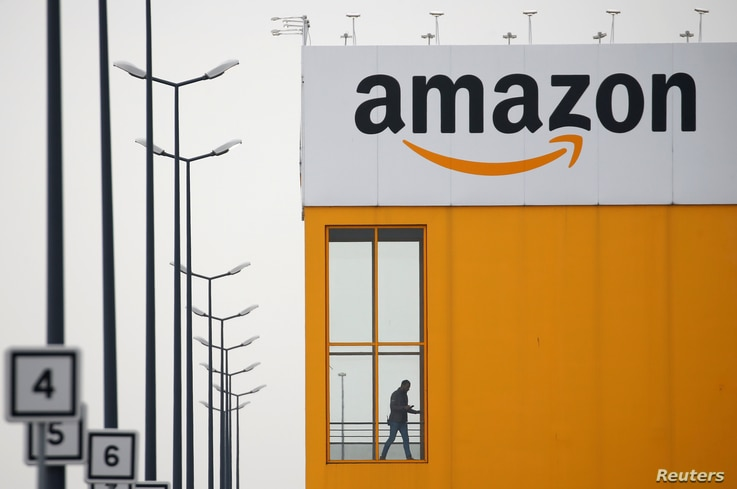 FILE PHOTO: The logo of Amazon is seen at the company logistics center in Lauwin-Planque, northern France, March 19, 2020…