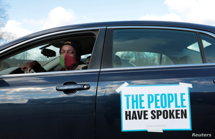 Tristan Taylor demonstrates in a car caravan as the Board of State Canvassers meet to certify the results of the election in…