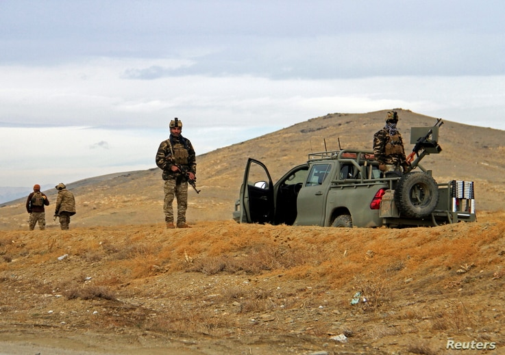 Afghan security forces keep watch outside of a military compound after a car bomb blast on the outskirts of Ghazni city,…