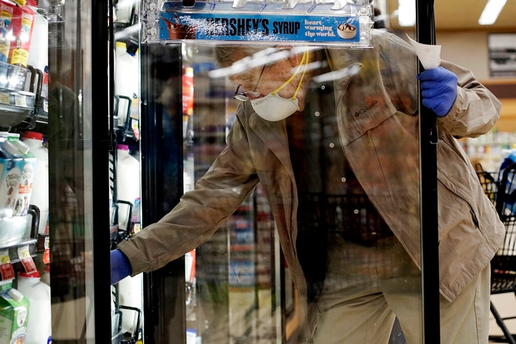 A shopper wears a mask and gloves to protect against coronavirus, as he shops at a grocery store in Mount Prospect, Illinois, May 13, 2020.