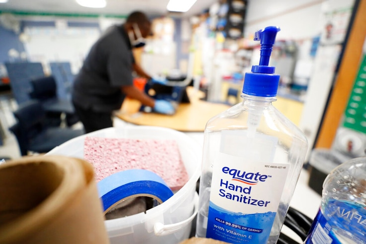 Hand sanitizer sits on a cart as Des Moines Public Schools custodian Tracy Harris cleans a chair at Brubaker Elementary School, July 8, 2020, in Des Moines, Iowa.