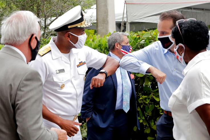 Surgeon General Dr. Jerome Adams, left, bumps elbows at Sergio's Restaurant in Doral, Florida, July 23, 2020.
