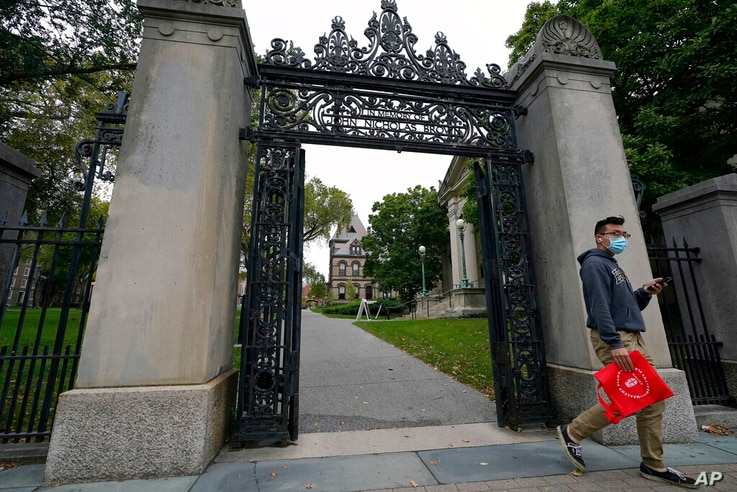 A passer-by departs a gate to the campus of Brown University, in Providence, R.I., Monday, Oct. 12, 2020. (AP Photo/Steven…