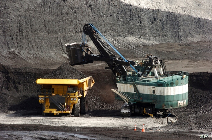 FILE - In this April 4, 2013, file photo, a mechanized shovel loads a haul truck with coal at the Spring Creek coal mine near…
