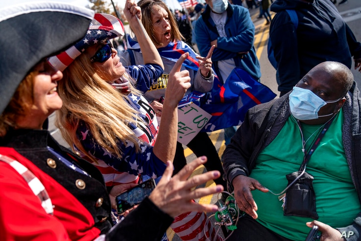 A Biden supporter who would only give his first name, Douglas, right, engages in a debate with Trump supporters demonstrating…