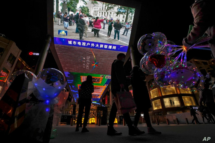 Shoppers walk by a woman selling balloons near a giant TV screen broadcasting a news of demonstrators protest against the U.S…
