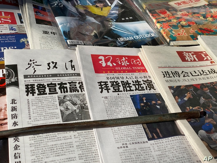 "Newspaper front-page with the headlines ""Biden wins"" are displayed at newsstand on Beijing, China, Monday, Nov. 9, 2020. As…"