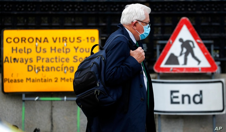 A man wearing a face mask walks past a Coronavirus sign during the second nationwide lockdown in London, Tuesday, Nov. 10, 2020…