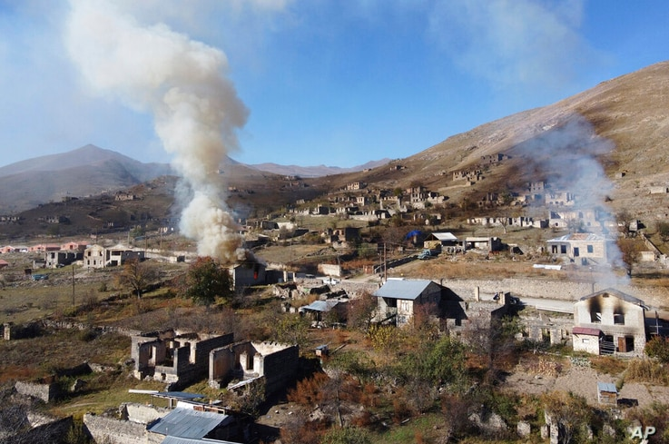 In this photo taken with a drone, smoke rises from burning houses as people leave the separatist region of Nagorno-Karabakh to…