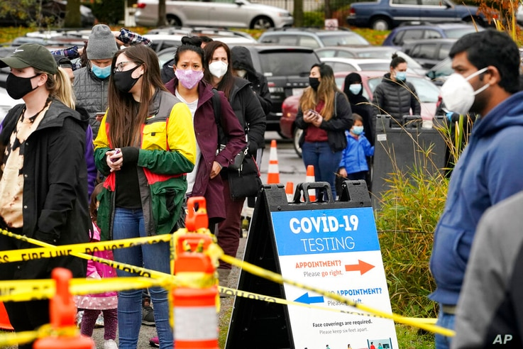 FILE - In this Nov. 18, 2020, file photo, people line up to be tested for the coronavirus at a free testing site in Seattle…