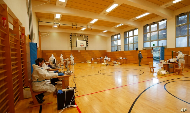 Medical staff members wait for citizens to be tested for coronavirus at a school gym that was set up as a testing facility in…