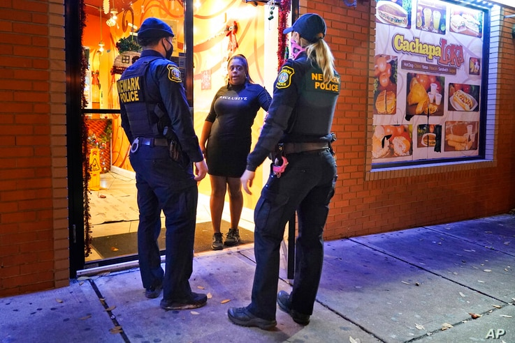 FILE - In this Nov. 12, 2020, file photo, police officers remind a woman in the doorway of a Newark, N.J., restaurant of the…