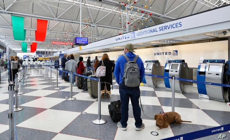 Des gens font la queue dans une zone United Airlines dans un terminal de l'aéroport international O'Hare de Chicago le vendredi 20 novembre 2020…