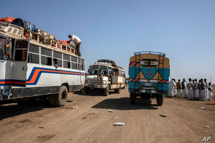 Sudanese men, right, help Tigray refugees who fled the conflict in the Ethiopia's Tigray, ride buses enroute to Qadarif to seek…