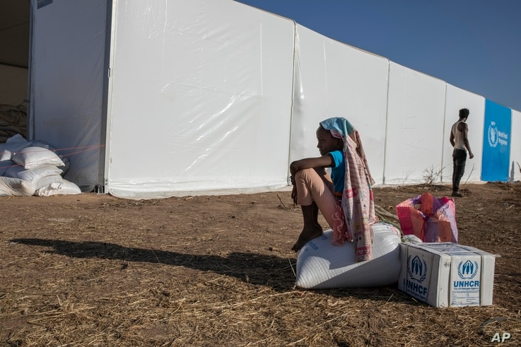 A Tigray refugee girl who fled the conflict in Ethiopia's Tigray region, sits on aid she received from the UNHCR and WFP at Umm…