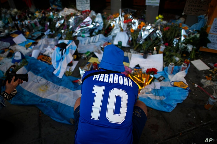 A fan mourns in front of flowers and posters left in tribute to Diego Maradona at the entrance of the Boca Juniors stadium…