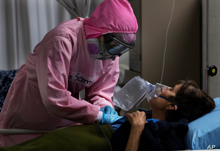 Dressed in protective gear to curb the spread of the new coronavirus, a medical worker massages a patient, at a military…