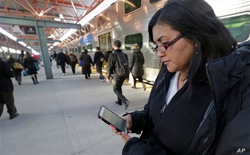 In this Friday, March 13, 2015 photo, Marilu Rodriguez checks a news website on her smartphone before boarding a train home at…