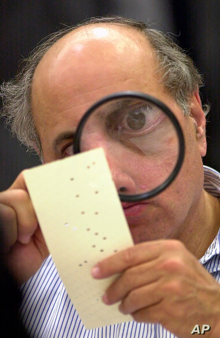 FILE - In this Nov. 24, 2000 photo, a magnifying glass is to examine a disputed ballot at the Broward County Courthouse in Fort Lauderdale, Florida recount.