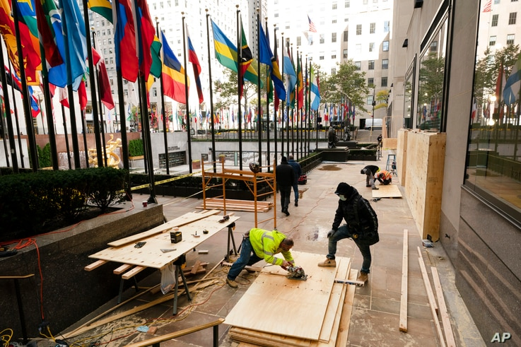 Workers board up a store in Rockefeller Center, Monday, Nov. 2, 2020, in New York ahead of Tuesday's contentious presidential…